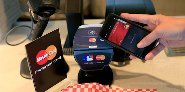 SAN FRANCISCO, CA - OCTOBER 24:  A fan uses MasterCard with Apple Pay to pay for garlic fries before Game Three of the 2014 World Series at AT&T Park on October 24, 2014 in San Francisco, California.  (Photo by Rob Carr/Getty Images for MasterCard)