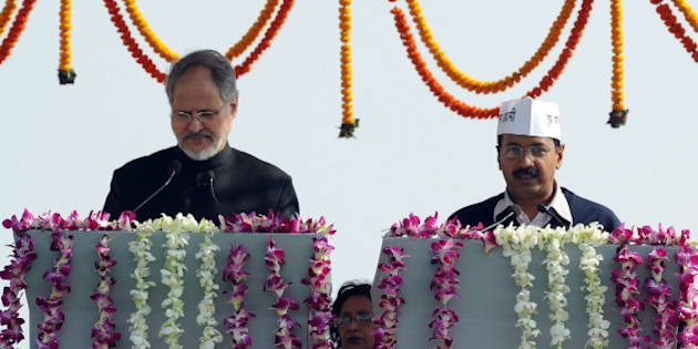 Anti-corruption champion and Aam Admi (Common Man) Party Leader Arvind Kejriwal (R) takes his oath of office as Chief Minister of India's national capital region from Delhi's Lt. Governor Najeeb Jung (L) at a ceremony in New Delhi on December 28, 2013, in what supporters hoped would mark a turning point in the nation's graft-ridden politics.  Cheers rang out as Kejriwal, who arrived for the ceremony on the city's subway, took the oath office in front of tens of thousands of supporters assembled in a Delhi park wearing white caps emblazoned with Kejriwal's slogan, 'I am a common man'. AFP PHOTO/RAVEENDRAN        (Photo credit should read RAVEENDRAN/AFP/Getty Images)