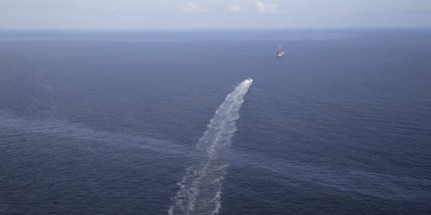 In this March 31, 2015 photo, the wake of a supply vessel heading towards a working platform crosses over an oil sheen drifting from the site of the former Taylor Energy oil rig in the Gulf of Mexico, off the coast of Louisiana. Down to just one full-time employee, Taylor Energy Company exists for only one reason: to fight a Gulf of Mexico oil leak that has gone largely unnoticed, despite creating miles-long slicks for more than a decade. (AP Photo/Gerald Herbert)