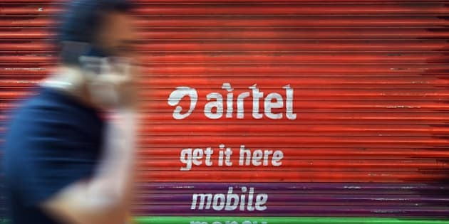 An Indian pedestrian talks on his cellphone while walking past advertising for a telecom service provider in Mumbai on April 17, 2015. India's telecoms regulator launched a consultation in March 2015 to determine new rules surrounding net neutrality, which the United States recently enshrined in law. Indian telecom operators say they are losing voice and text revenue to Internet applications that allow users to communicate at much cheaper costs. India has an estimated 185 million mobile Internet users according to a 2013 report by Mobile Landscape Survey, a US-based market research company, making it the world's third-biggest market after US and China.  AFP PHOTO/ Indranil MUKHERJEE        (Photo credit should read INDRANIL MUKHERJEE/AFP/Getty Images)