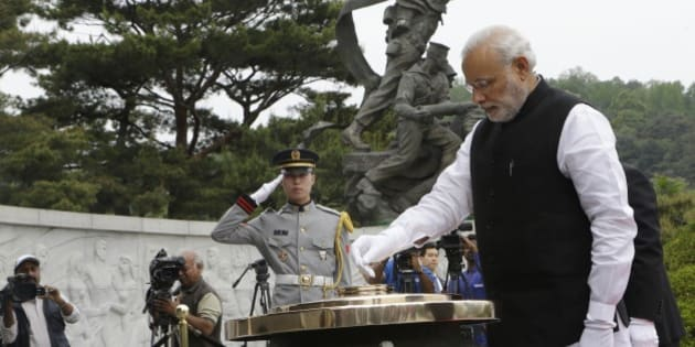Indian Prime Minister Narendra Modi, right, burns incense at the National Cemetery in Seoul, South Korea, Monday, May 18, 2015. Modi arrived Monday for a two-day visit to meet with South Korean President Park Geun-hye and to discuss economic ties and boost bilateral cooperation. (AP Photo/Ahn Young-joon)