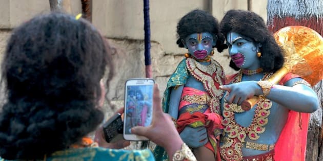 Indian artists dressed as monkey god Hanuman have a picture clicked on a mobile phone prior to Rama Navami festival at a temple in Bangalore on March 28, 2015.  Rama Navami is a Hindu festival, celebrating the birth of the god Rama whom Hindus consider is the seventh incarnation of Lord Vishnu and is the oldest known Hindu god having human form.  AFP PHOTO  / Manjunath KIRAN        (Photo credit should read Manjunath Kiran/AFP/Getty Images)