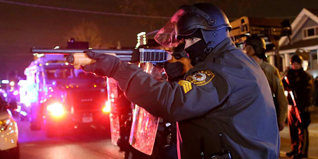 FERGUSON, MO - NOVEMBER 24:  A police officer points a shotgun at protestors during a demonstration on November 24, 2014 in Ferguson, Missouri. A St. Louis County grand jury has decided to not indict Ferguson police Officer Darren Wilson in the shooting of Michael Brown that sparked riots in Ferguson, Missouri in August.  (Photo by Justin Sullivan/Getty Images)
