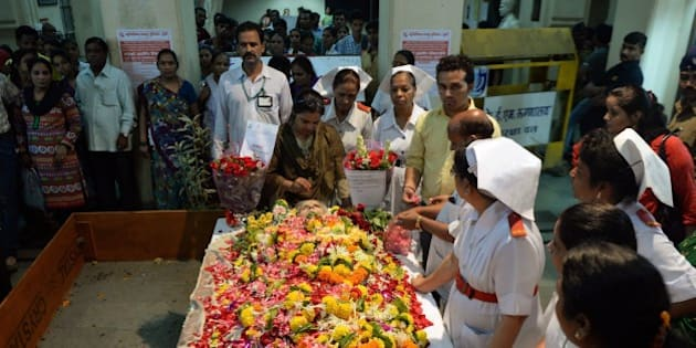 Indian nurses and hospital staff gather to pay their respect near the body of nurse Aruna Shanbaug at a hospital in Mumbai on May 18, 2015. Shanbaug died on May 18 after 42 years in a coma following a brutal rape, in a case that led India to ease some restrictions on euthanasia.  AFP PHOTO/ PUNIT PARANJPE        (Photo credit should read PUNIT PARANJPE/AFP/Getty Images)