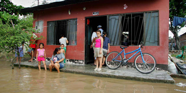 A Colombian family stands at the entrance of their home after heavy rains flooded their neighborhood on May 28, 2008, in Puerto Salgar, department of Cundinamarca, Colombia. The rains that have been battering Colombia since April have affected 100,000 people, leaving 11 dead and 33 wounded, according to official sources. Also, 370 houses were destroyed and 10,600 were damaged. AFP PHOTO/Mauricio DUE-AS (Photo credit should read MAURICIO DUENAS/AFP/Getty Images)