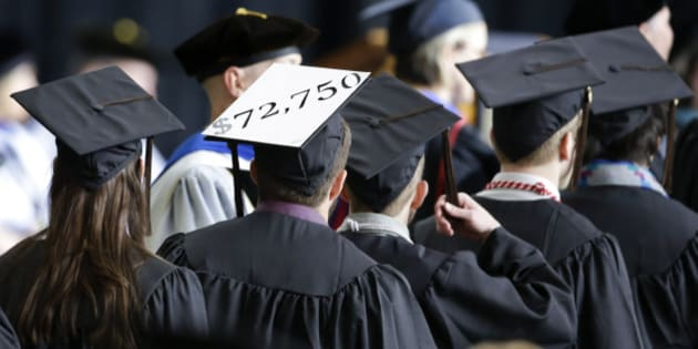 A student in line for his diploma wears a cap decorated with the cost of his education during graduation ceremonies at the University of Idaho in Moscow, Idaho., Saturday, May 16, 2015. (AP Photo/Orlin Wagner)