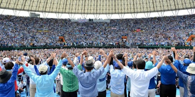 Some 35,000 protesters raise their hands during a rally to protest against a controversial US airbase in Naha in Japan's southern island of Okinawa on May 17, 2015. Futenma US airbase has become emblematic of that ill-will since Washington announced plans to move it in 1996, hoping to ease tensions with the host community after the gang-rape of a schoolgirl by servicemen. But locals have blocked the move to relocate the base, insisting the facility should go off-island instead, harming relations between Tokyo and Okinawa -- a once independent kingdom that was annexed by Japan in the 19th century.      JAPAN OUT   --  AFP PHOTO / JIJI PRESS        (Photo credit should read JIJI PRESS/AFP/Getty Images)