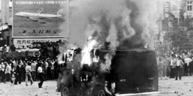 Student demonstrators watch a police vehicle burn near Seoul's South Gate on Thursday, May 15, 1980. More than 50,000 university students continued anti-government demonstration for the third straight day. (AP Photo)