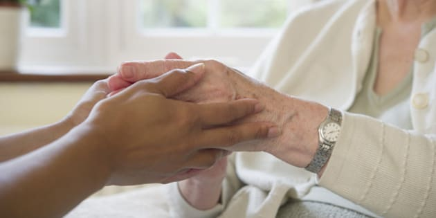 Close up of older woman and caretaker holding hands