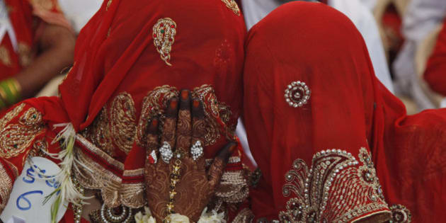 An Indian bride whispers to another during a mass marriage ceremony in Ahmadabad, India, Saturday, March 21, 2015. 112 Muslim couples from impoverished families tied the knot in a single ceremony organized by a social organization. (AP Photo/Ajit Solanki)