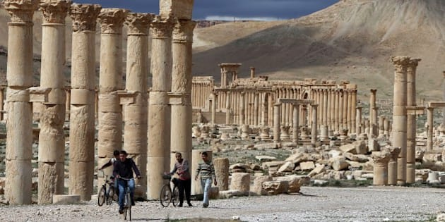 A picture taken on March 14, 2014 shows Syrian citizens riding their bicycles the ancient oasis city of Palmyra, 215 kilometres northeast of Damascus. From the 1st to the 2nd century, the art and architecture of Palmyra, standing at the crossroads of several civilizations, married Graeco-Roman techniques with local traditions and Persian influences. AFP PHOTO/JOSEPH EID        (Photo credit should read JOSEPH EID/AFP/Getty Images)