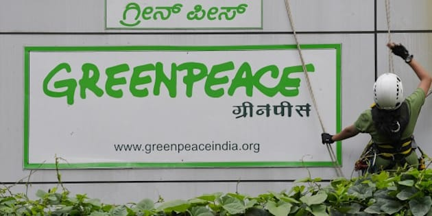 Activists of GreenPeace rappell down their office building where they are head quartered to unfurl banners 'democracy' and 'freespeech' in Bangalore on May 15, 2015.  Greenpeace India, which is on the verge of closing down after the Indian government blocked its domestic accounts, is planning to appeal to the judiciary for relief. The NGO recently told its employees that the threat of an imminent shutdown is looming large as it has been left with cash reserves for salaries and office costs for just about a month.  AFP PHOTO/ Manjunath KIRAN        (Photo credit should read Manjunath Kiran/AFP/Getty Images)