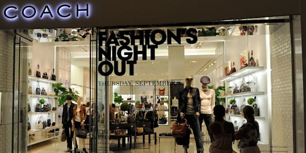 LAS VEGAS, NV - SEPTEMBER 08:  Customers look at a Coach store window during Fashion's Night Out at The Forum Shops at Caesars September 8, 2011 in Las Vegas, Nevada.  (Photo by Ethan Miller/Getty Images for The Forum Shops)