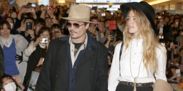"U.S. actor Johnny Depp and his fiancee Amber Heard arrive at Haneda international airport in Tokyo Monday, Jan. 26, 2015 for his latest film ""Mortdecai"" promotion. (AP Photo/Shizuo Kambayashi)"