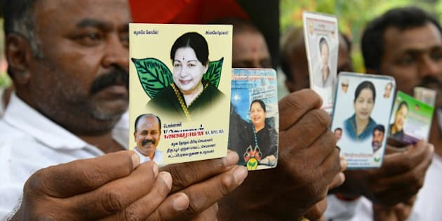 Supporters of All India Anna Dravida Munnetra Kazhagam (AIADMK) supremo, Jayalalithaa Jayaram as they wait to hear the verdict in the 18-year-old, disproportionate assets case in Bangalore on May 11, 2015.  The head of India's largest Tamil party was cleared of corruption May 11, 2015, a verdict that sparked wild celebrations by supporters and paved the way for the return of one of the country's most powerful politicians.     AFP PHOTO/ Manjunath KIRAN        (Photo credit should read Manjunath Kiran/AFP/Getty Images)