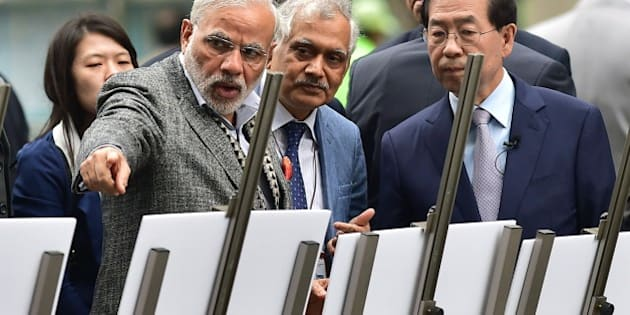 Indian Prime Minister Narendra Modi (L) talks with Seoul Mayor Park Won-Soon (R) as he visits the Cheonggye stream in central Seoul on May 19, 2015. Modi called on South Korea to be a 'leading partner' in his country's economic modernisation as he talked up investment opportunities at the start of a two-day visit. AFP PHOTO / JUNG YEON-JE        (Photo credit should read JUNG YEON-JE/AFP/Getty Images)