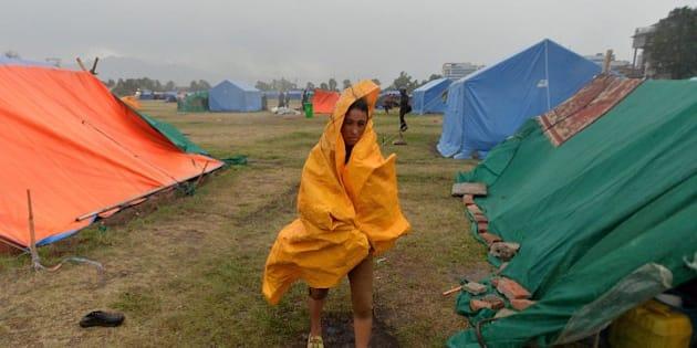 A Nepalese residents walks during a downpour at a relief camp for earthquake survivors in Kathmandu on May 23, 2015. Nearly 8,500 people have now been confirmed dead in two earthquakes which destroyed more than half a million homes and left huge numbers of people without shelter with just weeks to go until the monsoon rains.  AFP PHOTO / ISHARA S. KODIKARA        (Photo credit should read Ishara S.KODIKARA/AFP/Getty Images)