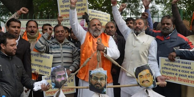 Rashtrawadi Shiv Sena (RSS) leader, Jai Bhagwan Goyal (C), with party activists,  holds the effigies of underworld don Dawood Ibrahim, who is wanted for the 1993 Mumbai bombings, (R), Pakistan chief of Jamaat-ud-Dawa, Hafiz Muhammad Saeed (C) and a leader of Lashkar-e-Taiba and 2008 Mumbai attacks accused, Zaki-ur-Rehman Lakhvi during a protest in New Delhi on December 21, 2014.  The protestors were demanding the handover of the three men.  AFP PHOTO / SAJJAD HUSSAIN        (Photo credit should read SAJJAD HUSSAIN/AFP/Getty Images)