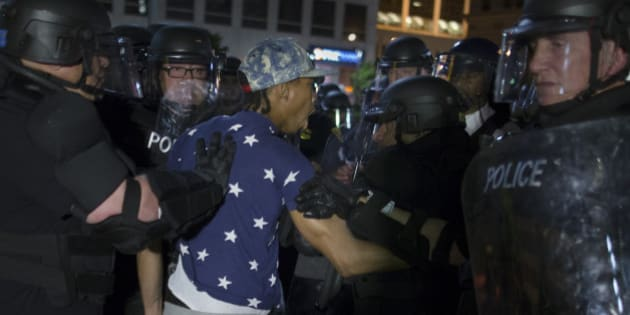 A demonstrator is arrested during a march against the acquittal of Michael Brelo, a patrolman charged in the shooting deaths of two unarmed suspects, Saturday, May 23, 2015, in Cleveland.  Brelo was acquitted Saturday in a case involving a 137-shot barrage of gunfire that helped prompt the U.S. Department of Justice determine the city police department had a history of using excessive force and violating civil rights. (AP Photo/John Minchillo)