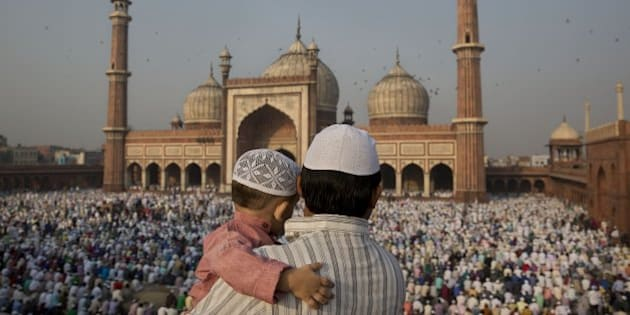 An Indian man carries a child as they gather to offer prayers at Jama Masjid mosque in New Delhi, India, Monday, Oct. 6, 2014. Muslims around the world celebrate Eid al-Adha, or the Feast of the Sacrifice, to commemorate the prophet Abraham's offering for his son to god. (AP Photo/Bernat Armangue)
