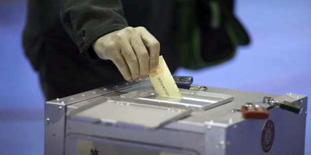 A man casts his vote for parliament's lower house election at a polling station in Tokyo, Sunday, Dec. 14, 2014. Japanese voters headed to the polls Sunday in a parliamentary election that is expected to reaffirm the ruling Liberal Democratic Party's majority, though many analysts were predicting a record low turnout. (AP Photo/Eugene Hoshiko)