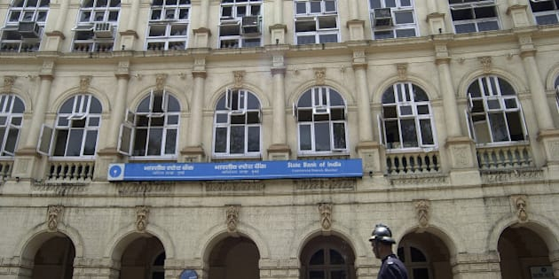 A fire fighter passes by a heritage building, which houses State bank of India, after it was partially damaged in a fire in Bombay, India, Sunday, April 16, 2006. No casualties were reported. (AP Photo/Aijaz Rahi)