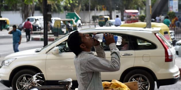 An Indian labourer takes a break as he drinks water to get respite from heat in New Delhi on May 26, 2015. At least 800 people have died in a major heatwave that has swept across India, melting roads in New Delhi as temperatures neared 50 degrees Celsius (122 Fahrenheit). AFP PHOTO/MONEY SHARMA        (Photo credit should read MONEY SHARMA/AFP/Getty Images)