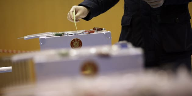 A man casts his vote in Japan's parliamentary elections at a polling station in Tokyo, Sunday, Dec. 14, 2014. Japanese voters headed to the polls Sunday in a parliamentary election that is expected to reaffirm the ruling Liberal Democratic Party's majority, though many analysts were predicting a record low turnout. (AP Photo/Eugene Hoshiko)