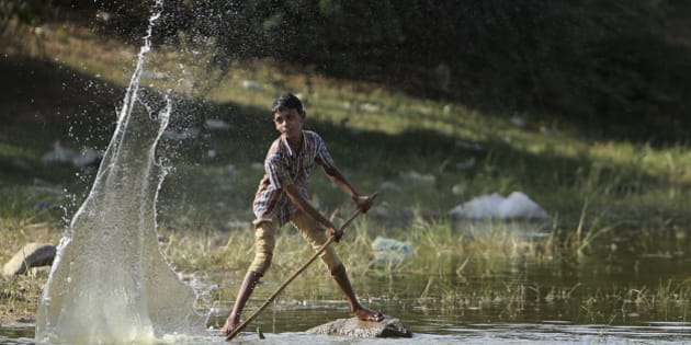 An Indian boy plays with water at a pond on a hot summer day in Hyderabad, India, Sunday, May 24, 2015. About 230 people have died since mid-April in a heat wave sweeping two southeast Indian states, Andhra Pradesh and Telangana, officials said Saturday. Day temperatures in Telangana's Khammam district soared to more than 48 degrees Celsius (118 Fahrenheit) on Saturday. (AP Photo/Mahesh Kumar A.)