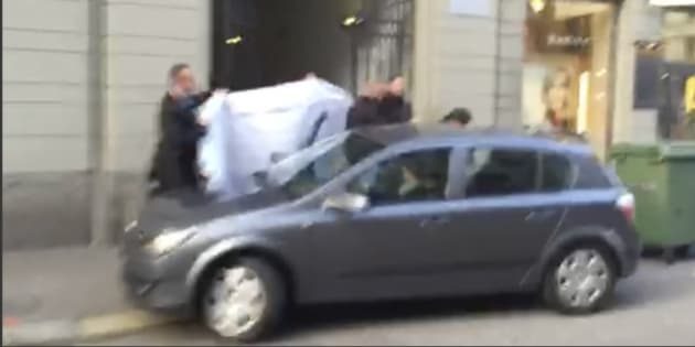 """Picture taken from a cell phone video shows hotel employees holding a blanked to hide the identity of a person led out of a side entrance of the Baur au Lac hotel to a waiting car in Zurich, Switzerland, Wednesday, May 27, 2015. Six soccer officials were arrested and detained by Swiss police on Wednesday pending extradition at the request of U.S. authorities after a raid in the luxury hotel. The case involves bribes """"totaling more than US$ 100 million"""" linked to commercial deals dating back to the 1990s for soccer tournaments in the United States and Latin America, the Swiss Federal Office of Justice said in a statement. (AP Photo/Rob Harris)"""