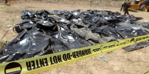 Body-bags containing the remains of people believed to have been slain by jihadists of the Islamic State (IS) group lie on the ground at the Speicher camp in the Iraqi city of Tikrit, on April 12, 2015. The Islamic State (IS) jihadist group executed hundreds of mostly Shiite recruits last June in what is known as the Speicher massacre, named for the military base near which they were captured. Thirteen grave sites have been found -- 10 in the palace complex and three outside, Haider Majid, an employee of Prime Minister Haider al-Abadi's office working on the Speicher issue, said.   AFP PHOTO / AHMAD AL-RUBAYE        (Photo credit should read AHMAD AL-RUBAYE/AFP/Getty Images)