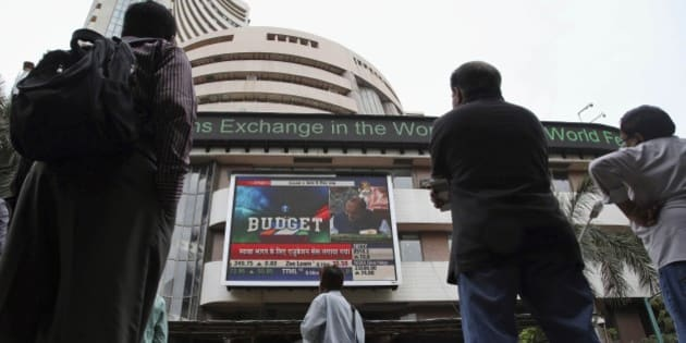 Indian people watch Indian Finance Minister Arun Jaitley make the union budget speech on a television screen  outside the Bombay Stock Exchange (BSE) in Mumbai, India, Saturday, Feb. 28, 2015. Jaitley announced the government's new budget on Saturday, promising a slew of measures that attempt to balance welfare spending with high economic growth and infrastructure development, while vowing to keep a tight control on fiscal deficit. (AP Photo/Rajanish Kakade)