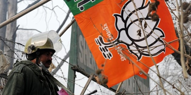 An Indian paramilitary soldier stands guard next to a Bharatiya Janata Party (BJP) campaign flag during a curfew in Srinagar on December 8, 2014. Prime Minister Narendra Modi is set to hit the campaign trail for regional elections in Indian Kashmir, just days after a militant attack left 11 soldiers and police dead. Hundreds of extra troops have been deployed in the main city Srinagar where Modi is due to speak at a public rally to boost his Hindu nationalist party's bold bid to seize power in the troubled Muslim-majority region. AFP PHOTO/Rouf BHAT        (Photo credit should read ROUF BHAT/AFP/Getty Images)