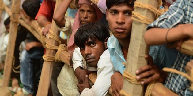 Supporters of Indian Prime Minister Narendra Modi look on as they wait for him to arrive at a rally venue in Mathura on May 25, 2015. Prime Minister Narendra Modi has vowed to improve the lot of India's beleaguered farmers, promising non-stop power and better irrigation, as he battles to win approval for a controversial land bill. At a mass rally to mark the first anniversary of his inauguration, Modi told thousands of supporters that he had attacked corruption in his first 12 months in office and ended the 'looting' of the country. AFP PHOTO/MONEY SHARMA.        (Photo credit should read MONEY SHARMA/AFP/Getty Images)