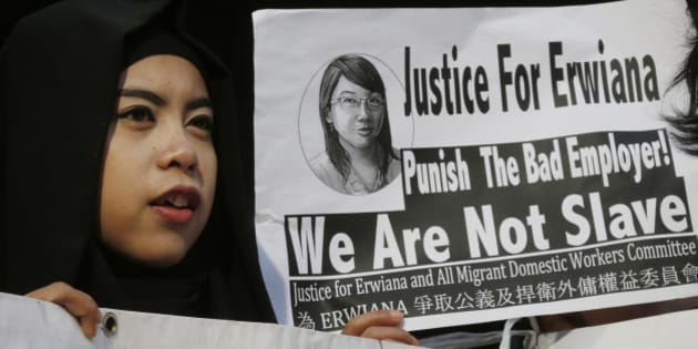 A supporter of Indonesian maid Erwiana Sulistyaningsih, holds a placard as Sulistyaningsih arrives at a court in Hong Kong, Tuesday, Feb. 10, 2015. A Hong Kong woman who was accused of torturing her Indonesian maid in a case that sparked outrage for the scale of its brutality was convicted of a slew of assault and other charges on Tuesday. A judge found Law Wan-tung guilty of 18 charges that also included criminal intimidation and failure to pay wages or give time off work to Sulistyaningsih. (AP Photo/Kin Cheung)