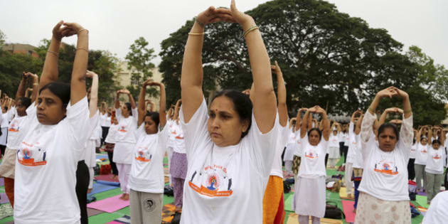 Yoga enthusiasts perform Surya Namaskar or sun salutation as they celebrate World Yoga Day in Bangalore, India, Saturday, June 21, 2014. The event was organized to create awareness among people about the benefits of yoga. (AP Photo/Aijaz Rahi)