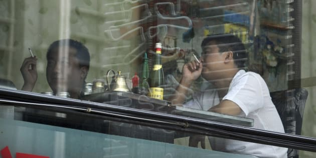 In this Saturday, July 24, 2010 photo, people smoke cigarettes inside a restaurant in Beijing. China has committed to banning smoking at public indoor venues by Jan. 9, 2011, in accordance with a global anti-tobacco treaty backed by the World Health Organization. But smoking is such a way of life that China is unlikely to meet the deadline. (AP Photo/Andy Wong)