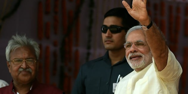 Indian Prime Minister Narendra Modi gestures to the crowd as he arrives at a rally venue in Mathura on May 25, 2015. Prime Minister Narendra Modi has vowed to improve the lot of India's beleaguered farmers, promising non-stop power and better irrigation, as he battles to win approval for a controversial land bill. At a mass rally to mark the first anniversary of his inauguration, Modi told thousands of supporters that he had attacked corruption in his first 12 months in office and ended the 'looting' of the country.  AFP PHOTO/MONEY SHARMA        (Photo credit should read MONEY SHARMA/AFP/Getty Images)