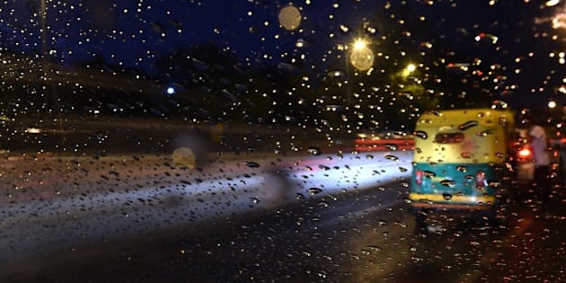 An Indian auto rickshaw is seen through a windshield of a car as a passenger gets on board while rain falls in New Delhi on June 1, 2015.   AFP PHOTO / SAJJAD HUSSAIN        (Photo credit should read SAJJAD HUSSAIN/AFP/Getty Images)