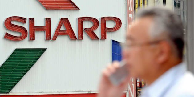 A man speaking on a mobile phone walks by a billboard of Sharp Corp. in Tokyo Thursday, July 31, 2008. Sharp posted a 2.8 percent rise in profit for the fiscal first quarter Thursday as healthy sales of liquid crystal displays for TVs and solar cells helped offset the damage from a strong yen. (AP Photo/Katsumi Kasahara)