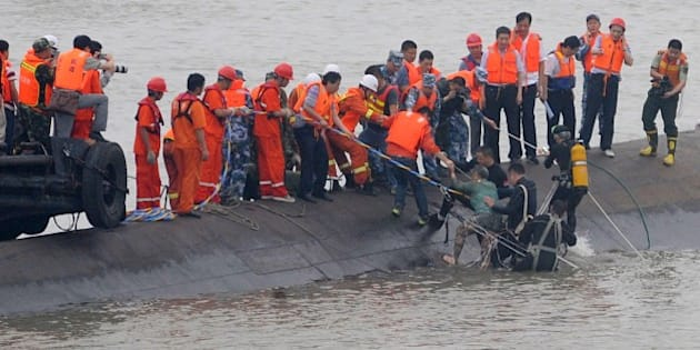 A survivor (C) is rescued by divers from the Dongfangzhixing or 'Eastern Star' vessel which sank in the Yangtze river in Jianli, central China's Hubei province on June 2, 2015. Divers raced to find survivors on June 2 after a Chinese ship sank with more than 450 mainly elderly people in the storm-tossed Yangtze river, raising hopes more people can be found alive. CHINA OUT AFP PHOTO        (Photo credit should read STR/AFP/Getty Images)