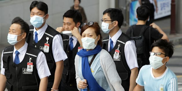 SEOUL, SOUTH KOREA - JUNE 02:  People wear masks as a precaution against the MERS virus on June 2, 2015 in Seoul, South Korea. The Ministry of Health and Welfare of South Korea confirmed two deaths from Middle East Respiratory Syndrome (MERS) on June 2, 2015. It reported six new cases of MERS, raising the number of confirmed local patients to 25. The first case was confirmed on May 20.  (Photo by Chung Sung-Jun/Getty Images)