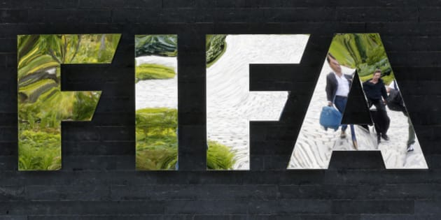 """Two persons are reflected in the FIFA logo at the FIFA headquarters in Zurich, Switzerland, Wednesday, May 27, 2015. Swiss prosecutors opened criminal proceedings into FIFA's awarding of the 2018 and 2022 World Cups, only hours after seven soccer officials were arrested Wednesday pending extradition to the U.S. in a separate probe of """"rampant, systemic, and deep-rooted"""" corruption. (AP Photo/Michael Probst)"""