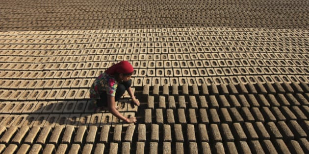 An Indian woman laborer works at an earthen brick factory on Earth Day on the outskirts of Jammu, India, Wednesday, April 22, 2015. The world marks Earth Day on April 22 to increase awareness and to promote practices for the sustainability and protection of the Earth's natural environment. (AP Photo/Channi Anand)