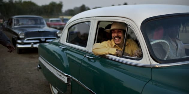 Indian businessman Ahsok Kaicker smiles as he drives in his vintage 1953 Chevrolet Bel-Air during a display in a break at the Cavalry Gold Cup Polo match at the Jaipur Polo Grounds in New Delhi, India, Sunday, Dec. 12, 2010. (AP Photo/Kevin Frayer)