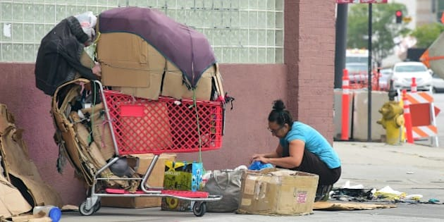 A homeless woman packs up her belongings after a night sleeping on the street in Los Angeles, California on May 12, 2015. A report released by the Los Angeles Homeless Authority on May 11 showed a 12% increase in the homeless population in both Los Angeles city and county, which according to the report have been driven by soaring rents, low wages and stubbornly high unemployment. One of the most striking findings from the biennial figures released saw the number of makeshift encampments, tents and vehicles occupied by the homeless increased 85%.  AFP PHOTO / FREDERIC J. BROWN        (Photo credit should read FREDERIC J. BROWN/AFP/Getty Images)