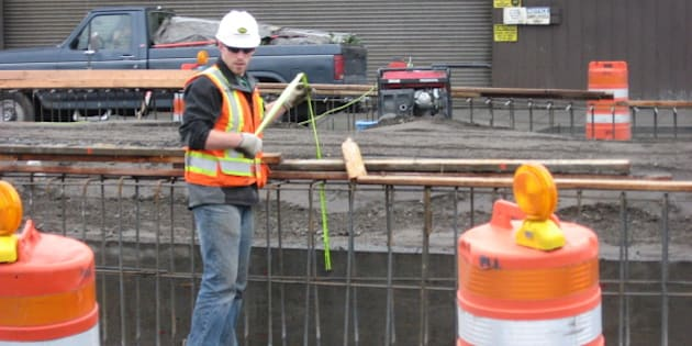 "This worker is ""measuring twice and cutting once."" He's working on the new First Avenue S ramp from the Spokane Street Viaduct."