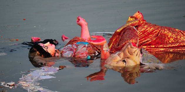An idol of the Hindu goddess Durga floats in a temporary pond near Sangam after immersion in Allahabad on October 4, 2014.  The Durga Puja festival commemorates the slaying of a demon king Mahishasur by goddess Durga, marking the triumph of good over evil. AFP PHOTO/SANJAY KANOJIA        (Photo credit should read Sanjay Kanojia/AFP/Getty Images)