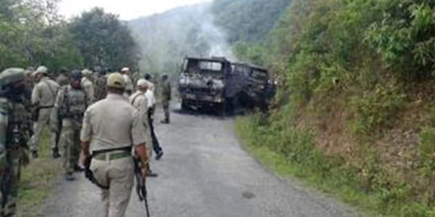 This photograph taken on June 4, 2015 shows Indian security personnel and smoldering vehicle wreckage at the scene of an attack on a military convoy in a remote area of Chandel district, about 120 kilometres (75 miles) southwest of northeastern India's Manipur's state capital Imphal. Heavily armed rebels in India's restive northeast killed at least 20 troops on June 4, police said, in one of the area's worst such attacks in years. AFP PHOTO        (Photo credit should read STR/AFP/Getty Images)