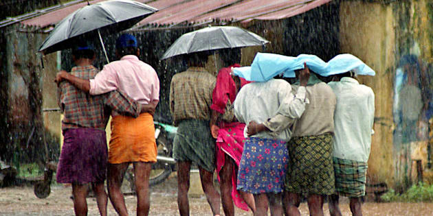 Fishermen walk under umbrellas and plastic sheets in the rain at the Cochin Harbor in Cochin, in the southern Indian state of Kerala, Wednesday, June 25, 2003. Kerala has been witnessing heavy southwest monsoons for the past week. (AP Photo)